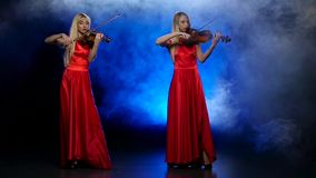 Two girls blonde to play the fiddle. Smoky background with backlight. Slow motion. Two blonde girls, with long hair, playing the violin professional, long red stock video footage