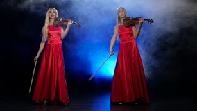 Two girls blonde to play the violin. Smoky background with backlight. Slow motion. Two blonde girls, with long hair, playing the violin professional, long red stock footage