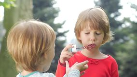 Two girls are blowing bubbles in the park, Slow stock footage