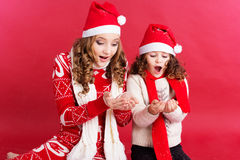 Two girls are blowing fake snow Stock Photography