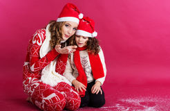 Two girls are blowing fake snow in studio Stock Photo