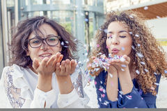 Two girls blowing some confetti piece Royalty Free Stock Photography