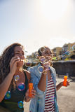 Two girls blowing strings of bubbles Royalty Free Stock Photos