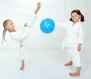 Two girls with blue ball beat karate kick Stock Images