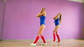 Two girls in blue bathing suits dance against the background of a purple wall. Girls in the disco style are dancing sexy stock video footage