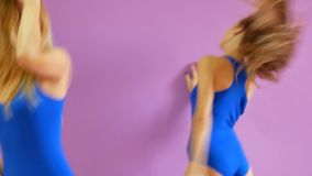 Two girls in blue bathing suits dance against the background of a purple wall. Girls in the disco style are dancing sexy stock footage