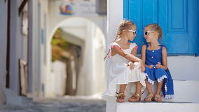 Two girls in blue dresses having fun outdoors. Kids at street of typical greek traditional village with white walls and stock footage
