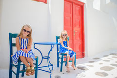 Two girls in blue dresses sitting on blue chairs and table on street of typical greek traditional village with white Royalty Free Stock Photo