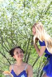 Two girls in blue in the garden Stock Images