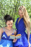 Two girls in blue are reading in the garden Stock Photo