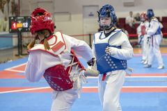Two girls in blue and red Taekwondo equipment are fighting at doyang. Two girls in blue and red Taekwondo equipment fight in doyang in Taekwondo competitions stock images