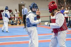 Two girls in blue and red Taekwondo equipment fight in doyang in Taekwondo competitions royalty free stock photo