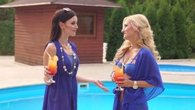 Two girls talking with cocktails by the pool. Two girls in blue swimsuits with cocktails in their hands talking while standing by the pool. Summer rest. Hotel stock video