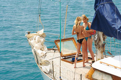Two girls on a boat cruise. Two young girls are sailing on a yacht Royalty Free Stock Photos