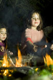 Two girls at a bonfire Royalty Free Stock Photos