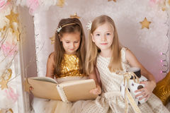 Two girls with a book. Christmas time Stock Photos