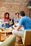 Two girls and boy chat in cafe Royalty Free Stock Photos