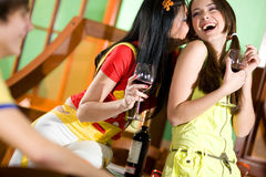 Two girls and boy are drinking wine Stock Images