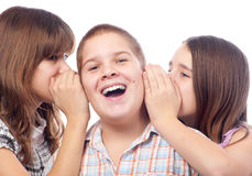 Two girls and a boy gossiping Stock Images
