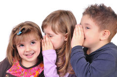 Two girls and a boy gossiping Royalty Free Stock Image