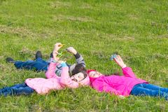 Two girls and a boy lie on the grass and play spinner stock photography