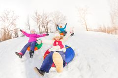 Two girls and boy slide on colorful tubes together. Two girls and boy slide on colorful tubes with arms up during beautiful winter day with trees trunks on the Stock Photos