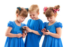 Two girls and a boy with their cell phones Royalty Free Stock Photos