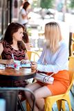 Two girls at a business breakfast in a cafe. Two girls at a breakfast business in a cafe on a street on a sunny day royalty free stock images