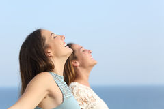 Two girls breathing deep fresh air on the beach. Two girls doing breath exercises inhaling fresh air on the beach Stock Images