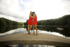 Two Girls on a Bridge. Best friends forever. Two happy young women dressed in red, embrace in friendship Stock Photos