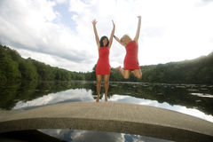Two Girls on a Bridge Jump for Joy. Best friends forever. Two happy young women dressed in red, jump for joy on a bridge Royalty Free Stock Photos