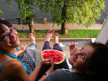 Two girls brunettes eating watermelon sitting on the windowsill and his legs dangling down,St. Petersburg, Russia, August 2011 Stock Images