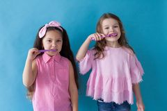 Two little girls brush their teeth toothbrushes dentistry royalty free stock photos