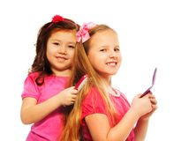 Two girls brushing hair. Two girls Caucasian and Asian playing to be big like older sisters brushing each other hair, isolated on white, full length portrait Stock Photo
