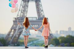 Two girls with bunch of balloons in front of the Eiffel tower. Two beautiful girls with bunch of pink and blue balloons in front of the Eiffel tower in Paris Royalty Free Stock Photo