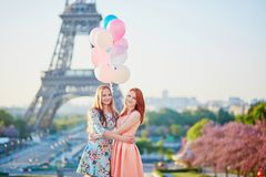Two girls with bunch of balloons in front of the Eiffel tower. Two beautiful girls with bunch of pink and blue balloons in front of the Eiffel tower in Paris Royalty Free Stock Images