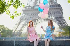 Two girls with bunch of balloons in front of the Eiffel tower. Two beautiful girls with bunch of pink and blue balloons in front of the Eiffel tower in Paris Stock Photos