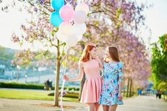 Two girls with bunch of balloons in front of the Eiffel tower. Two beautiful girls with bunch of pink and blue balloons in front of the Eiffel tower in Paris Stock Photography