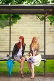 Two Girls at Bus Stop. Rainy day stock photo