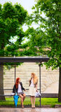 Two Girls at Bus Stop. Rainy day royalty free stock photography