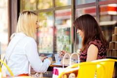 Two girls at a business breakfast in a cafe. Two girls at a breakfast business in a cafe on a street on a sunny day royalty free stock photography