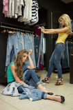 Two girls buy jeans in the store. tired girlfriend. Two beautiful girls buy jeans in the store. tired girlfriend royalty free stock images