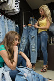 Two girls buy jeans in the store. tired girlfriend Royalty Free Stock Images