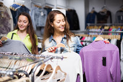 Two girls buying sweater in a shop Stock Photos