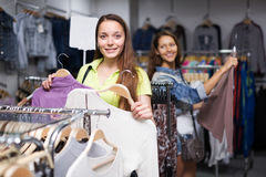 Two girls buying sweater in a shop Stock Images