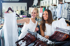 Two girls buying tops in clothes store Stock Photo