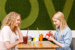 Two girls in cafe with present Royalty Free Stock Images