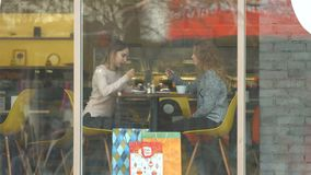 Two girls in a cafe. Slow motion. Two girls are sitting in a cafe behind the glass stock video