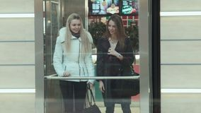 Two girls came into elevator and go down in mall. Two girls came into the elevator and go down in mall stock footage