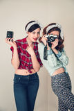 Two girls. With cameras in retro style stock photography